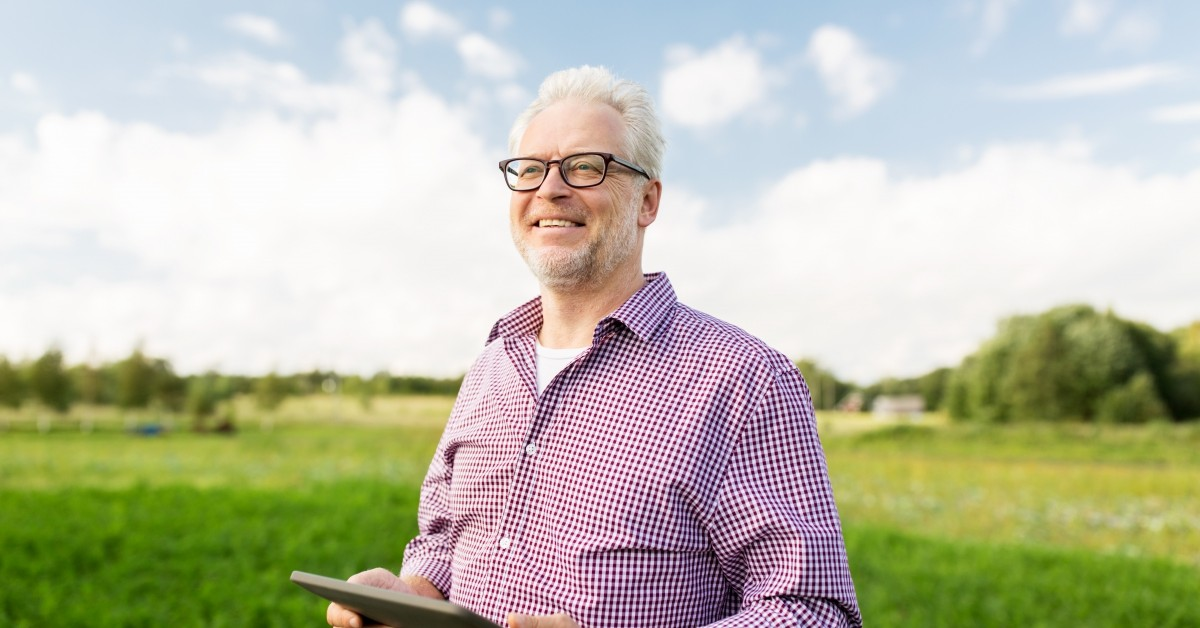 A smiling man stands in a field