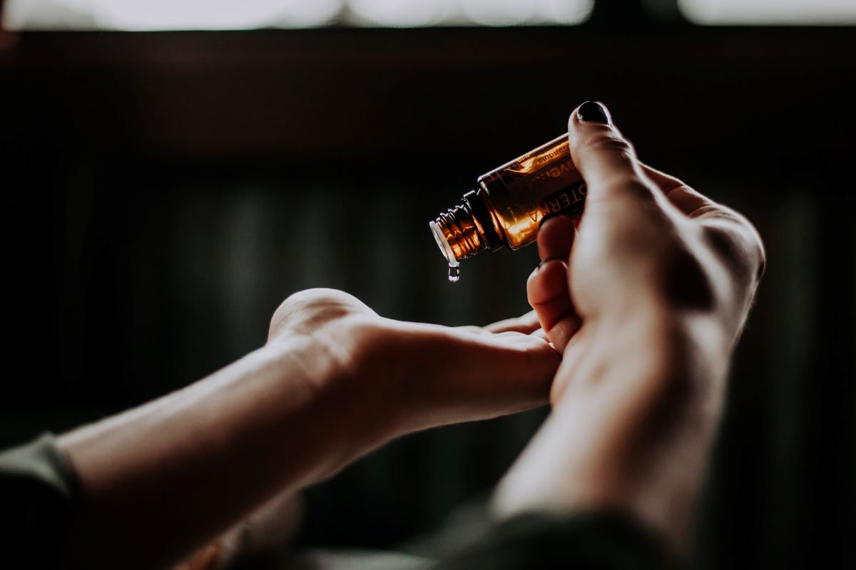 Person holding amber glass bottle and pouring out a medicinal tincture. Photo by Christin Hume on Unsplash.